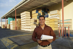 man-clipboard-standing-front-timber-factory-portrait-happy-middle-aged-33897732